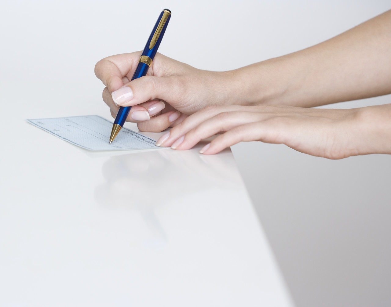 Woman Writing a Check --- Image by © Royalty-Free/Corbis